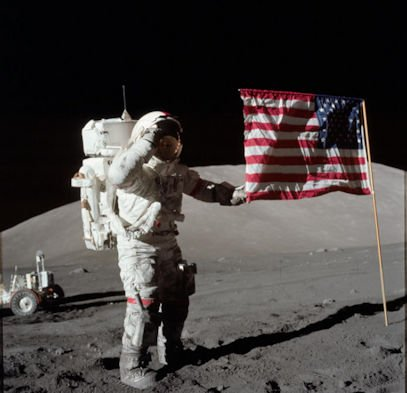 Apollo 17 Astronaut Eugene A. Cernan is photographed next to the deployed United States flag on December 7, 1972. NASA image.