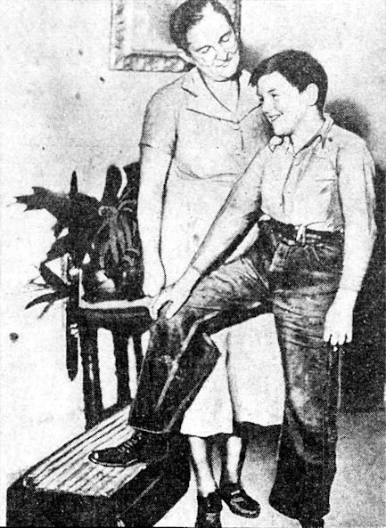 Eleven-year-old Earl Baker with his new artificial leg. His mother looks on.