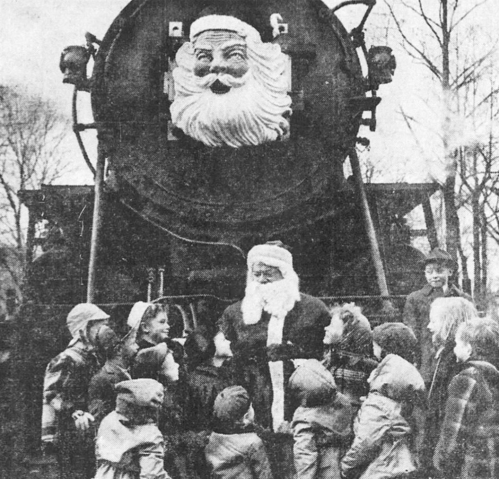 Santa with children in front of the Santa Heim Express locomotive.