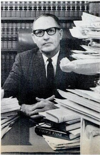 Judge Robert L. Myers seating behind a stack of letters received from claimants all around the world.