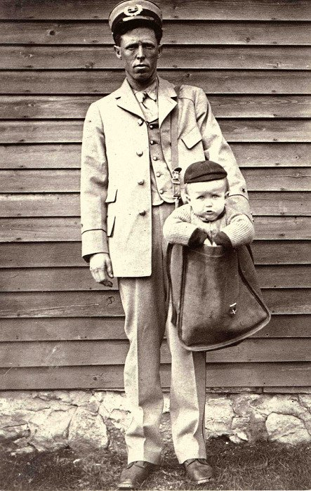 Letter carrier posed for a humorous photograph with a young boy in his mailbag.