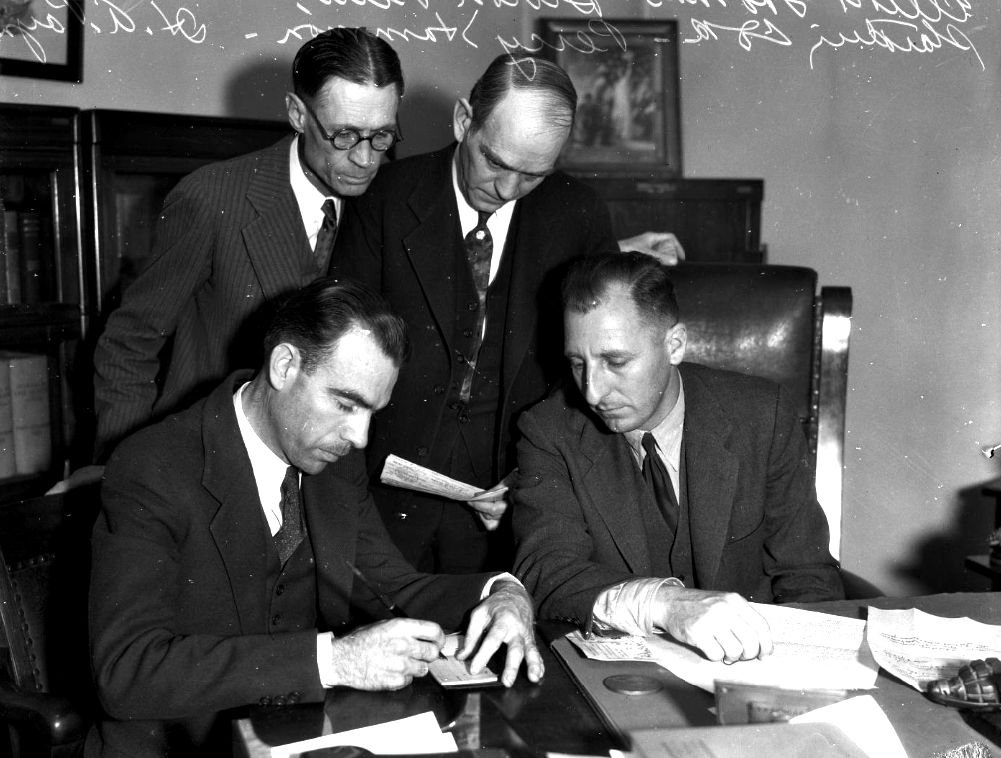 Buron Fitts, Percy Starmmon, and Herbert Payne watch as Elliot B. Thomas signs a check, Los Angeles, 1932.