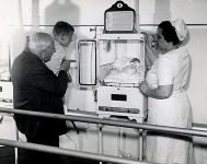 Martin Couney, his daughter Hildegarde, and a boy look at a baby in an incubator.