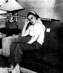 Joan Frances Hiles sitting on her couch. The dashed line shows the path of the bullet.