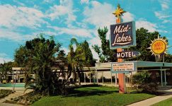 Vintage motel postcard advertising air conditioning, telephones, and TV.